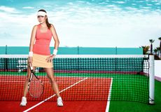 Beautiful redhead fit sport girl with a racket on. Full length portrait of a young woman on a tennis dross field royalty free stock photo