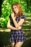 Beautiful redhead on a forest road. Beautiful redhead in mini dress posing on a forest road, in nature, fashion and pin up photography Stock Photos