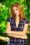 Beautiful redhead on a forest road. Beautiful redhead in mini dress posing on a forest road, in nature, fashion and pin up photography Royalty Free Stock Image