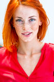 Beautiful redhead freckled woman. Smiling seductive, biting lips Stock Image