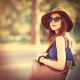 Beautiful redhead girl with bag in the park. Royalty Free Stock Photo