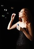 Beautiful redhead girl blows bubbles. Studio portrait, profile view Royalty Free Stock Photo