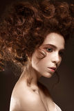 Beautiful redhead girl with curls and classic make-up. Beauty face. Photo was made in studio Stock Image