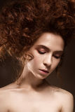 Beautiful redhead girl with curls and classic make-up. Beauty face. Photo was made in studio Stock Images