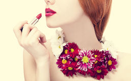 Beautiful redhead girl with flowers holding lipstick Stock Photography