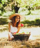Beautiful redhead girl with fruits in basket. At garden royalty free stock images