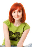 Beautiful redhead girl in green t-shirt. And earrings stock photography