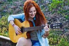 Beautiful redhead girl with guitar Royalty Free Stock Image