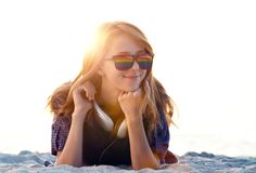 Beautiful redhead girl with headphones at beach sand. royalty free stock photography
