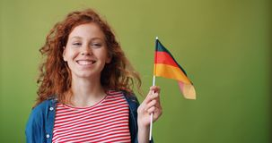 Beautiful redhead girl holding German flag smiling on green background. Beautiful redhead girl hipster is holding German flag smiling standing on green stock footage
