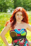 Beautiful redhead girl with long hair outdoors Stock Images