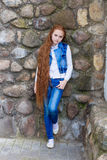 Beautiful redhead girl with long hair up to knees. Posing outdoors Stock Image