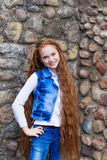 Beautiful redhead girl with long hair up to knees. Posing outdoors Stock Photo