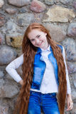Beautiful redhead girl with long hair up to knees. Posing outdoors Stock Photography
