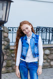 Beautiful redhead girl with long hair up to knees. Posing outdoors Stock Images