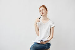 Beautiful redhead girl making notes thinking sitting over white background. Royalty Free Stock Photos