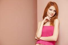 Beautiful redhead girl near wall. Royalty Free Stock Image