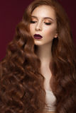Beautiful Redhead girl with a perfectly curls hair and classic make-up. Beauty face. Stock Image
