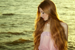 Beautiful redhead girl at pond royalty free stock photo