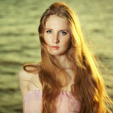 Beautiful redhead girl at pond royalty free stock photography