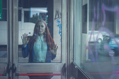 Beautiful redhead girl posing behind a glass door Royalty Free Stock Photo