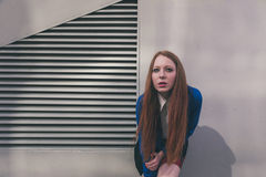 Beautiful redhead girl posing in an urban context Stock Image