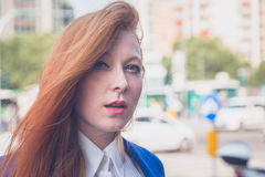 Beautiful redhead girl posing in an urban context Royalty Free Stock Photography
