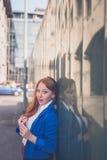 Beautiful redhead girl posing in an urban context Stock Photo