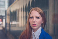 Beautiful redhead girl posing in an urban context Stock Images