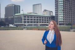 Beautiful redhead girl posing in an urban context Stock Photos