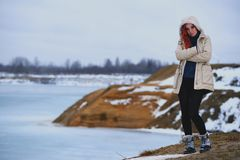 Beautiful redhead girl stays against Nordic landscape Stock Images