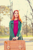 Beautiful redhead girl with suicase Stock Photo