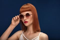 Beautiful redhead girl in sunglasses on blue background. stock images