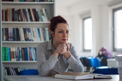 Beautiful redhead girl thinking on the desk with book and booksh Stock Photography