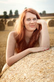 Beautiful redhead girl topless with a hay bale Royalty Free Stock Photo