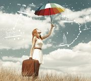 Beautiful redhead girl with umbrella and suitcase at outdoor. Stock Photo