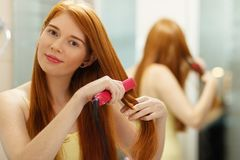 Beautiful Woman Ironing Healthy Red Hair With Iron Straightener. Beautiful redhead girl using electric hair straightener in bathroom. Pretty woman ironing hair Stock Images
