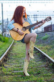 Beautiful redhead girl walk on railway with guitar. Royalty Free Stock Image
