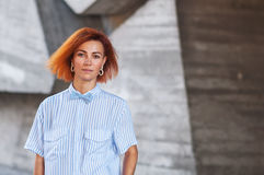 Beautiful redhead girl wearing in a striped shirt posing against background of concrete wall. Stock Photography