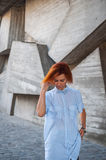 Beautiful redhead girl wearing in a striped shirt posing against background of concrete wall. Royalty Free Stock Images