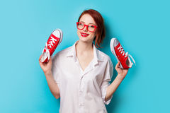 Beautiful redhead girl in white shirt with gumshoes Royalty Free Stock Image