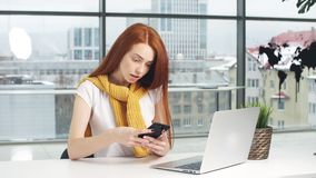 Beautiful redhead girl, working in the office, uses a laptop and mobile phone. Beautiful redhead girl, working in the office, uses a laptop and mobile phone stock video footage