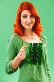 Beautiful redhead with green beer on St Patricks Day. Photo of a beautiful redhead woman holding and drinking a huge green beer Royalty Free Stock Photos