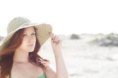 Beautiful redhead with a hat. A beautiful woman at the beach wearing a large hat Stock Images