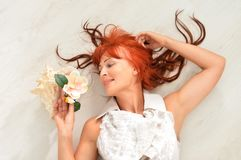 Portrait of beautiful redhead mature woman posing. Beautiful redhead mature woman posing with flower royalty free stock image
