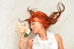 Portrait of beautiful redhead mature woman posing. Beautiful redhead mature woman posing with flower royalty free stock images