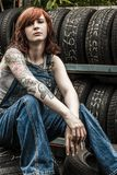 Beautiful redhead mechanic with tattoos. Photo of a young beautiful redhead mechanic wearing overalls and sitting behind an old garage. Attached property release Royalty Free Stock Photography