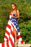 Beautiful redhead model draped in American Flag. Royalty Free Stock Photo
