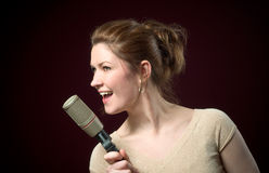 Beautiful Redhead Model Singing into Microphone. Beautiful Redhead Model Singing into Gold Microphone on deep red background Royalty Free Stock Images