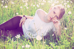 Beautiful redhead in nature. Beautiful redhead in white shirt and leggings lying in a grass, on a meadow, fashion photography, cross processing Royalty Free Stock Image